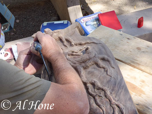 Al is using his power tool to do some wood carving outside