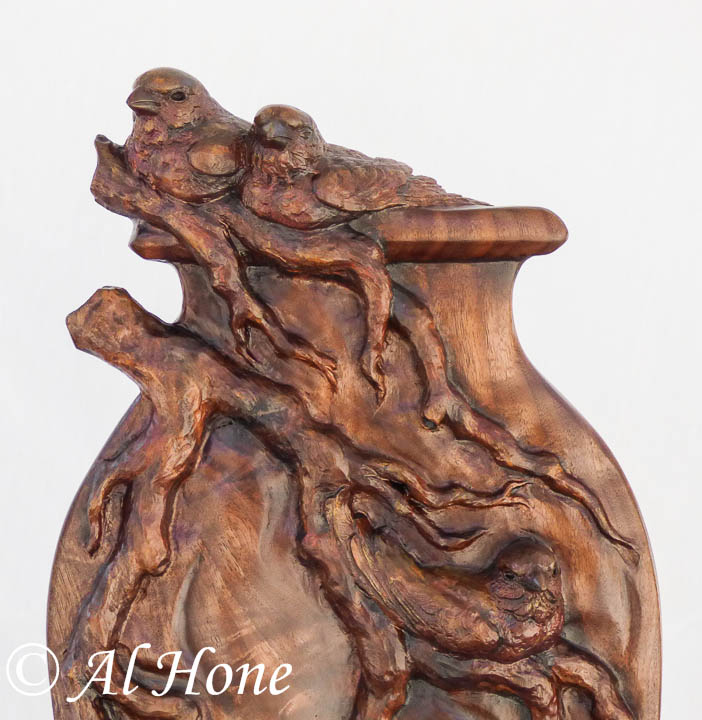 Wood sculpture of finches on a branch