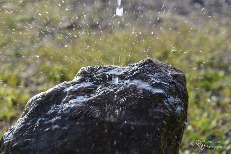 Water being poured on a rock and splashing
